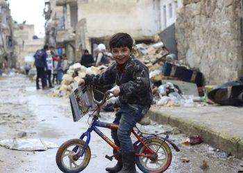 In This picture taken in January 2017 and provided by UNICEF, a Syrian child rides his bike while carrying manuals distributed by UNICEF volunteers in the area following an information session on identifying and reporting unexploded objects, at Al- Sakhoor neighbourhood, east Aleppo, Syria. The U.N.'s child relief agency says at least 652 children were killed in Syria last year, making 2016 the worst year yet for the country's rising generation. UNICEF says schools, hospitals, playgrounds, parks, and homes across the country are unsafe for children and come frequently under attack. (Khudr Al-Issa/ UNICEF via AP )