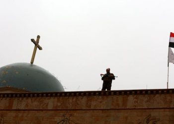 epa05688107 An Iraqi soldier stands guard during Christmas celebrations at the al-Tahira al-Kubra church in the formerly IS held town of al-Hamdaniya, some 13km east of Mosul, Iraq, 25 December 2016. Hundreds of Iraqi Christians held their prayers at a church in the recently recaptured town of Hamdaniya, for the first time since 2014, with the attendance of the US-led coalition officers and senior Iraqi officers.  EPA/AHMED JALIL