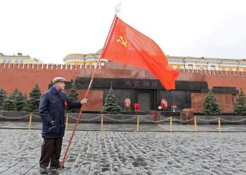 epa03189352 An old Russian communist holds a Soviet Red flag during the flower laying ceremony to the Lenin mausoleum on the Red square in Moscow, as they celebrate the 142nd anniversary of Lenin's birthday, in Russia, Russia, 20 April  2012. Vladimir Lenin, a founder of the Russian Communist party and father of the communist revolution in Russia buried as a mummy on the central capital Red Square.  EPA/SERGEI ILNITSKY