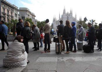 Persone in coda per un Taxi in piazza del Duomo a Milano. Autobus e metropolitane sono ferme a causa di uno sciopero  indetto dai  lavoratori di Atm, l'azienda del trasporto pubblico milanese, che si asterranno dal lavoro per quattro ore. Milano  5 aprile 2017. ANSA / MATTEO BAZZI