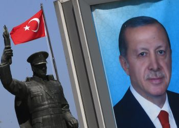 In this Tuesday, April 4, 2017 photo, backdropped by a statue of modern Turkey's founder Mustafa Kemal Ataturk, left, a poster of Turkey's President Recep Tayyip Erdogan for the upcoming referendum, is seen in his hometown city of Rize, in the Black Sea region, Turkey. Erdogan, whose family came originally from the village, one of the most transformational, polarising figures in modern Turkish history, is hoping that pious Muslim bedrocks of support, like his hometown region,will help deliver him a win in Turkey's April 16 referendum. (AP Photo/Lefteris Pitarakis)