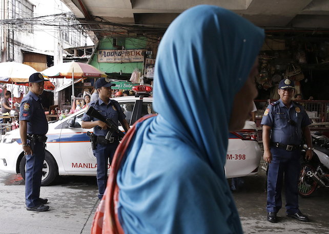 A Muslim woman passes by policemen at a checkpoint in downtown Manila, Philippines on Wednesday, May 24, 2017 as the Philippine National Police is placed under full alert status following the declaration of martial law in Mindanao southern Philippines. Philippine President Rodrigo Duterte warned Wednesday that he'll be harsh in enforcing martial law in his country's south as he abruptly left Moscow to deal with a crisis at home sparked by a Muslim extremist siege on a city, where militants burned buildings overnight and are feared to have taken hostages. (AP Photo/Aaron Favila)