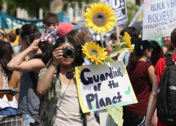 epa05936036 A woman shoots photos as protesters march from the US Capitol to the White House in Washington, DC, USA, 29 April 2017.  Thousands of demonstrators turned out for the Peoples Climate March which also marks the 100th day in office for US President Donald J. Trump.  EPA/TASOS KATOPODIS