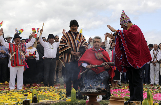 Ecuador's President Lenin Moreno, sitting, participates in symbolic swearing-in ceremony with representatives of Ecuador's indigenous leaders and Bolivia's President Evo Morales, in Cochasqui, Ecuador, Thursday, May 25, 2017. Cochasqui is an important place for ceremonies, traditional dances, shamanistic rituals, and marriages as well as the most extensive and most important complex of Pre-Columbian and pre-Inca Empire ruins in northern Ecuador. (AP Photo/Dolores Ochoa)
