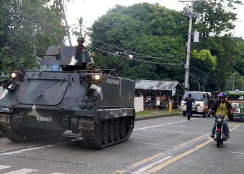A tank stops on the side of the road as it waits for other tanks to roll into a military camp in Iligan city to reinforce Government troops who are battling Muslim militants who laid siege in Marawi city for over a week now Wednesday, May 31, 2017 in southern Philippines. Fighting continues for the second week now between Government troops and Muslim militants with casualties on both side and civilians.(AP Photo/Bullit Marquez)
