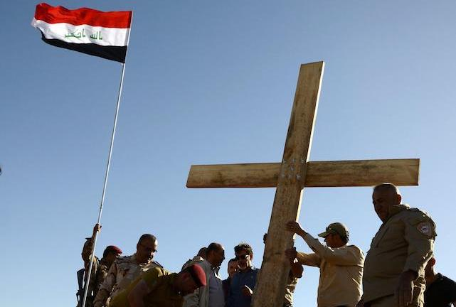 epa05926820 Muslims and Christians Iraqi civilians from Mosul raise a wooden cross near the monastery of Saint Mar Georges in Mosul, northern Iraq, 24 April 2017. (Issued 25 April 2017). A group of activists civilans from Mosul city raised a big wooden cross on the occasion of the birth of Saint Mar Georges in Mosul. It is a message of love and peaceful coexistence between communities in the city of Mosul, an Iraqi activist said.  EPA/OMAR ALHAYALI