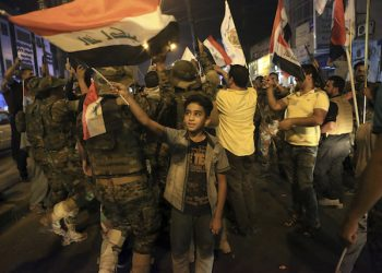 Iraqi security and civilians celebrate while holding national flags as they wait for the final announcement of the defeat of the Islamic state militants, in Basra, 340 miles (550 kilometers) southeast of Baghdad, Iraq, Sunday, July 9, 2017. Backed by the U.S.-led coalition, Iraq launched the operation to retake Mosul from Islamic State militants in October. (AP Photo/Nabil al-Jurani)
