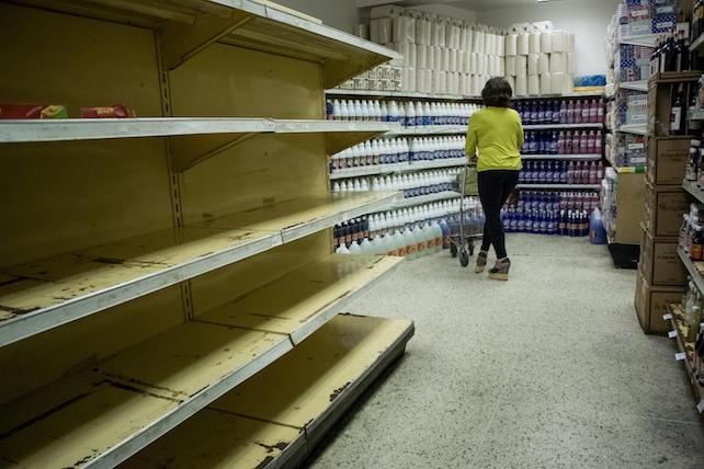 epa05155581 A woman shops in a supermarket in Caracas, Venezuela, 11 February 2016. Venezuelan Parliament has declared the 'National food crisis' and called the UN agencies FAO and Uniced to assess the risk of scarcity in the Venezuelan population.  EPA/MIGUEL GUTIERREZ