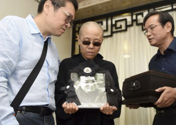 In this photo provided by the Shenyang Municipal Information Office, Liu Xia, center, wife of jailed Nobel Peace Prize winner and Chinese dissident Liu Xiaobo, holds a portrait of him during his funeral at a funeral parlor in Shenyang in northeastern China's Liaoning Province, Saturday, July 15, 2017. China says the body of Liu Xiaobo, who died this week after a battle with liver cancer, has been cremated. The government of the city of Shenyang in northeastern China, where Liu was treated, said in a briefing that the cremation took place Saturday morning in a ceremony attended by family and friends. (Shenyang Municipal Information Office via AP)