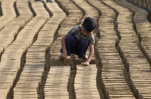 epa05184244 A boy works at a brick kiln on the outskirts of Lahore, Pakistan, 27 February 2016. The provincial government of Punjab enacted a new ordinance titled 'Punjab Prohibition of Child Labor at Brick Kilns Ordinance 2016' in January 2016, prohibiting the employment of children under the age of 14 years at brick kilns. The ordinance prohibits owners from employing, engaging or permitting a child to work at a brick kiln.  EPA/RAHAT DAR