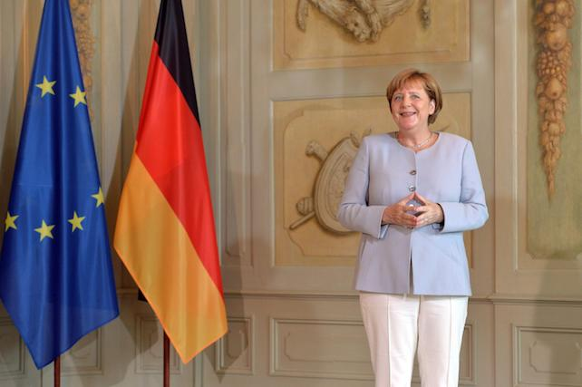 epa05420916 A smiling German Chancellor Angela Merkel stands next to a European Union (EU) and a German national flag as she waits for the arrival of the guests during a reception of the Diplomatic Corps at the German government's guesthouse in Meseberg, Germany, 11 July 2016.  EPA/MAURIZIO GAMBARINI