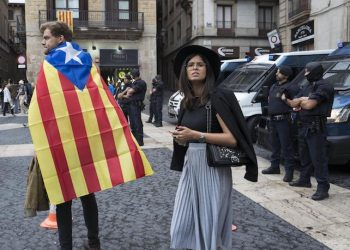 epa06238031 A couple with a Catalonian flag near Spanish police in the Placa Sant Jaume, or the Town Hall Square, in Barcelona, Spain 01 October 2017. Catalonia is holding an independence referendum which has been declared illegal by the Spanish Constitutional Court.  EPA/JIM HOLLANDER