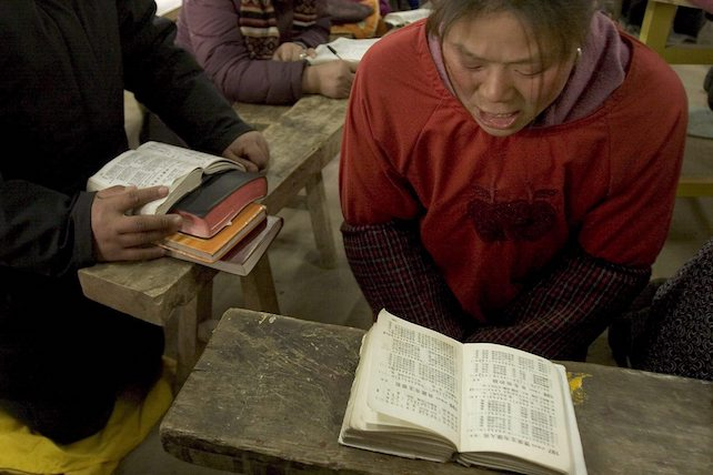 CINA: PREGHIERA IN CHIESA CRISTIANA.   Church member prays and sings on her knees during a service at a rural Christian church in northern Jiangsu Province in this fiel picture dated 11 February 2006 and made available 18 February. The church serves a 1,500-person congregation and has daily services. The congregation is comprised of 80 percent women, mostly very poor.  Although the actual number of Christians in China is difficult to verify, current conservative estimates are at over 60 million people and growing, making China home to one of the larger Christian communities in the world.  Ariana Lindquist  ANSA-CD