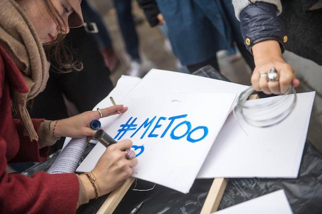 epa06296916 A woman writes the '#Metoo' slogan on a placard during a rally against gender-based and sexual violence against women, in Paris, France, 29 October 2017. The hashtag #MeToo was established in social networks aimed to encourage women to denounce their case of alleged sexual abuse.  EPA/CHRISTOPHE PETIT TESSON