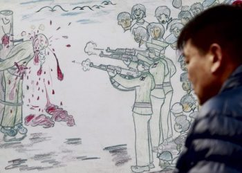 epa03028732 A Sourth Korean man looks at a  caricature depicting a public execution in North Korea, during a rally against North Korea's human rights policy in Seoul, South Korea, 09 December 2011. The rally is staged as part of a worldwide demonstration for North Korean liberation and human rights. The event was also held in 10 other nations, including the US, Japan, Britain and Kenya, on the occasion of the 63rd anniversary of the United Nations Genocide Convention.  EPA/JEON HEON-KYUN