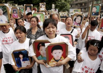 epa01364675 Parents and loved ones mourn for children that perished in the 12 May 2008 earthquake at the Xinjian Primary School, where about 300 students died according to parents, in Dujiangyan, Sichuan province, China, 01 June 2008. As China observes Children's Day 01 June 2008, a ceremony was held on at the ruins of the school and parents wore shirts that said 'Severely punish those responsible for the shoddy construction of the Xinjian Primary School... Justice for the dead pupils.'  Family members brought pictures of the fallen children and burned incense, candles and wept at the ceremony.  The official death toll of the earthquake has nearly reached 70,000 and many people are infuriated that so many schools collapsed while neighboring buildings stood.  EPA/MICHAEL REYNOLDS