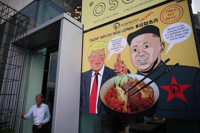 epa06788443 A man exits a door next to a poster depicting US President Donald J. Trump (C), North Korean leader Kim Jong-Un (R), and a promotional dish of 'Trump-Kim Chi Nasi Lemak' at a restaurant in Singapore, 06 June 2018. The White House has confiremd that US President Donald J. Trump and North Korean leader Kim Jong-un will meet at the Capella Hotel for their expected historic summit on 12 June 2018.  EPA/WALLACE WOON