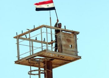 epa06871805 A Syrian soldier hoists the national flag atop a monitoring tower in Nassib border crossing in the southeastern countryside of Daraa city in south Syria, 07 July 2018. According to media reports, the Syrian army seized control on the crossing on the Syrian-Jordanian borders a day earlier. The crossing has a strategic importance and is considered Syria's southern gate and a main transport and economic hub.  EPA/YOUSSEF BADAWI