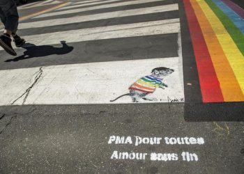epa06846917 A close-up shows a message of the French organisation for Medically assisted procreation, 'La procreation medicalement assistee' (PMA) that reads, 'PMA for all the love without end' as people walk by rainbow pedestrian crossing decorations in a street of the Marais neighborhood in Paris, France, 28 June 2018. Those crossroad have been restored after being targeted by homophobic vandals. Anne Hidalgo, mayor of Paris, has declared that the Pride decorations stay permanently. The Paris LGBT Pride will take place on 30 June.  EPA/CHRISTOPHE PETIT TESSON