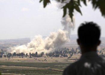 epa06903963 Smoke rises as Syrian rebels allegedly burn buildings they used and detonate their ammunitions before getting on the busses to leave to the northern Syrian city of Idlib from the city of Quneitra by the Syrian-Israeli borders in the Golan Heights, as seen from the Israeli side of the border, 22 July 2018. The Syrian army backed by Russian air strikes launched an offensive on the rebels-held southwestern provience of Quneitra during the same month. Rebels and the Syrian army reached an agreement that allows rebels and their family to leave to the rebels-control northern city of Idlib. According to reports, Israel Defense Forces (IDF) evacuated some 800 of the Syrian Civil Defense (Also known as the White Helmets) and their families from Quneitra to Jordan at the request of the United States and several European countries, the reports also added that the IDF is not intervening in the ongoing conflict in Syria.  EPA/ATEF SAFADI