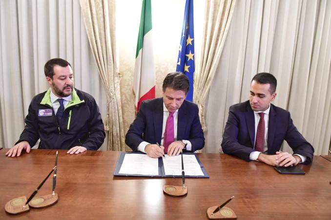 Il premier Giuseppe Conte firma il decreto sicurezza tra i due vice Matteo Salvini e Luigi Di Maio