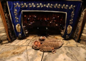 epa07215160 A visitor placed a baby at the Grotto inside the Church of the Nativity, built atop the site where Christians believe Jesus Christ was born, on Christmas Eve, in the West Bank city of Bethlehem, 07 December 2018. The Church of the Nativity, built on the site where Jesus Christ is believed to have been born in the West Bank city of Bethlehem, is administered jointly by Greek Orthodox, Roman Catholic, Armenian Apostolic and Syriac orthodox church.  EPA/ABED AL HASHLAMOUN
