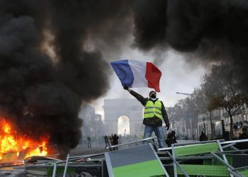 A demonstrator waves the French flag onto a burning barricade on the Champs-Elysees avenue with the Arc de Triomphe in background, during a demonstration against the rise of fuel taxes, Saturday, Nov. 24, 2018 in Paris. French police fired tear gas and water cannons to disperse demonstrators in Paris Saturday, as thousands gathered in the capital and staged road blockades across the nation to vent anger against rising fuel taxes and Emmanuel Macron's presidency.(ANSA/AP Photo/Michel Euler) [CopyrightNotice: Copyright 2018 The Associated Press. All rights reserved.]