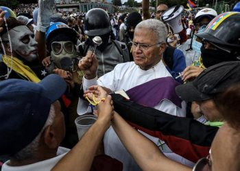 epa06048617 A priest blesses protesters during a demonstration called 'Venezuela gives a message to the Armed Force' in Caracas, Venezuela, 24 June 2017. The Venezuelan opposition marched to the military bases of the Capital while chavists commemorated the 196th anniversary of the Carabobo battle.  EPA/Miguel GutiÈrrez