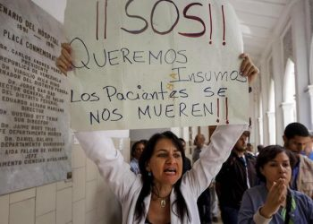 epa06726269 A woman holds a sign that reads 'SOS, we want supplies, patients are dying' as she joins fellow health workers and patients protesting at the Hospital Dr. Jose Maria Vargas in Caracas, Venezuela, 10 May 2018. Patients and medical workers protested at the Hospital over the worsening of health services. During the demonstration, a group of people identified as Chavistas followers burst into the place, preventing journalists and demonstrators from leaving the place.  EPA/EDWINGE MONTILVA