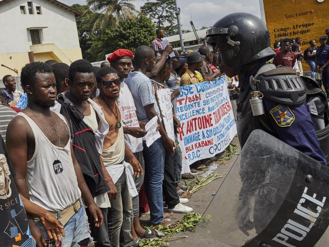 epa07300812 Supporters of DR Congo's President-elect Felix Tshisekedi face with a police officer as they protest outside the constitutional court examining an appeal from a runner-up candidate Martin Fayulu, who is disputing the results of fraught elections, in Kinshasa, the Democratic Republic of the Congo, 19 January 2019. Tshisekedi's party rejected the unprecedented request by African Union to delay the announcement of the final result, as the court is set to give a ruling on late 19 January.  EPA/HUGH KINSELLA CUNNINGHAM