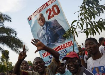 epa07271963 Supporters of DR Congo's opposition candidate for the Presidential election, Felix Tshisekedi, the leader of the Union for Democracy and Social Progress (UDPS) party, rally outside his party headquarters in Limete, Kinshasa, as they wait for the electoral commission to announce the provisional results, in Democratic Republic of the Congo, 09 January 2019. Riot police officers have been deployed at the commission headquarters amid fears of violence as the country awaits for the the announcement of the Presidential election result.  EPA/HUGH KINSELLA CUNNINGHAM