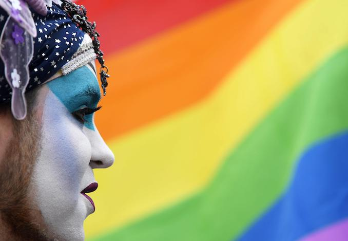 epa05311531 An activist of the lesbian, gay, bisexual and transgender†(LGBT) movement named 'Sister†Dominique' in front of a rainbow flag during an event held in front of the state parliament in†Potsdam, Germany, 17 May 2016. The rainbow flag is flying in front of the Brandenburg state parliament on the same day. The flag has been popularised worldwide as a symbol of the LGBT†movement.  EPA/RALF†HIRSCHBERGER