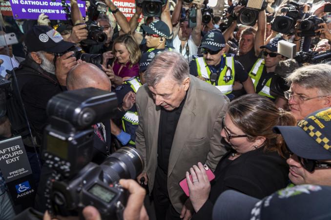 Il cardinale George Pell tra fotografi e polizia all'ingresso del tribunale di Melbourne