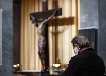 Un uomo con mascherina contro il coronavirus in preghiera in una chiesa di Roma