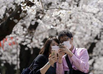 Coppia con protezione anti coronavirus davanti allo smartphone