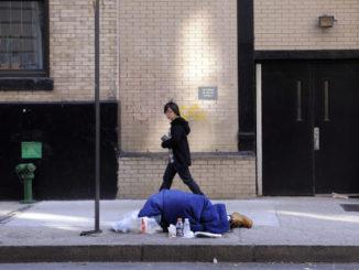 Homeless sdraiato lungo un marciapiede a New York