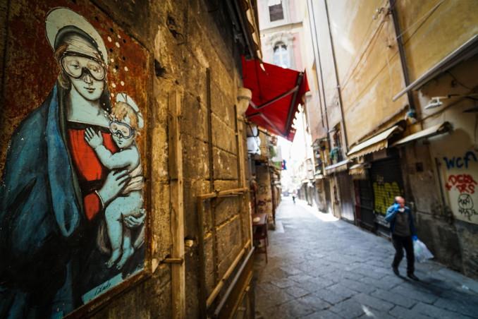 Madonna e Gesù bambino con protezioni anti coronavirus in un murale a Napoli
