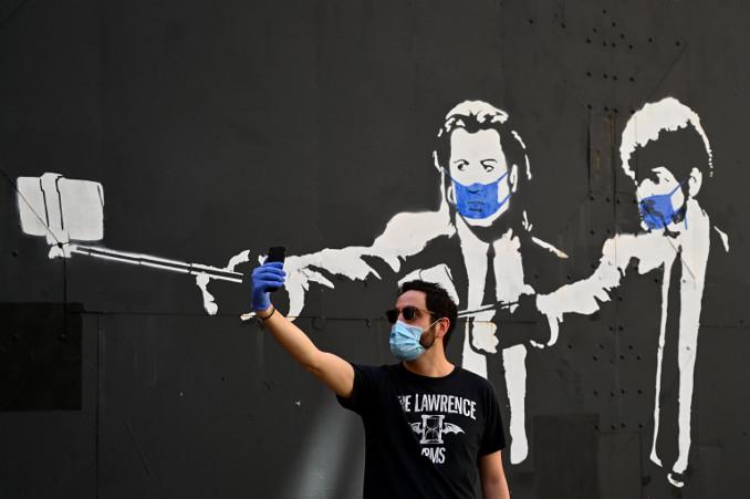Selfie davanti a un murale di Pulp Fiction in versione emergenza coronavirus