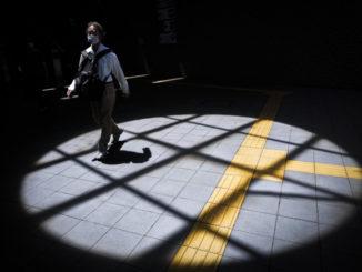 Un uomo con mascherina durante il distanziamento sociale in Giappone per l'emergenza coronavirus