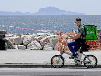 Rider effettua consegne in bicicletta sul lungomare di Napoli