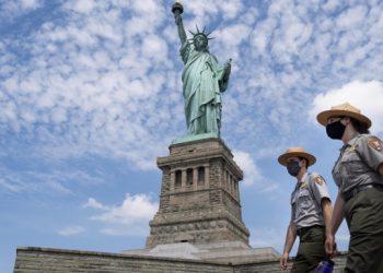 Agenti di sicurezza sorvegliano la statua della libertà a New York durante l'emergenza coronavirus