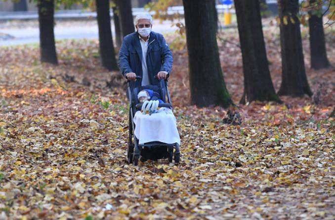 Nonno e nipote neonato passeggiano in un parco di Milano durante il lockdown