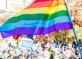 Manifestazione con bandiera arcobaleno e manifesto pro Biden