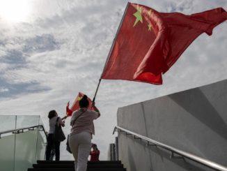Una donna festeggia a Hong Kong con la bandiera cinese l'anniversario dell'handover