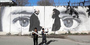 Bambini davanti a un murale che celebra gli accordi di pace di Doha tra Usa e Afghanistan