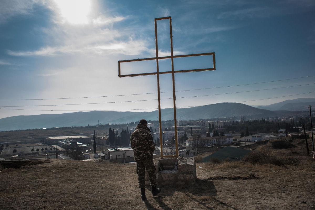 Soldato armeno prega davanti a una croce a Martakert, Nagorno-Karabakh