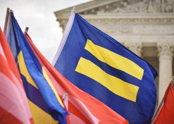 Bandiera con simbolo di uguale a una manifestazione per uguaglianza fra generi-sessi