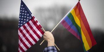 Un uomo sventola la bandiera degli Stati Uniti e quella Lgbt