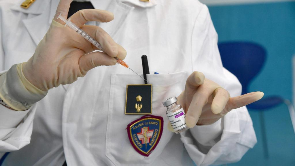Agente di polizia somministra vaccino AstraZeneca