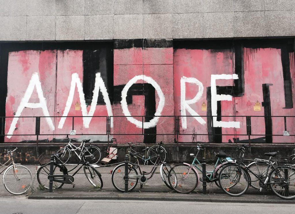 biciclette parcheggiate davanti a un murales
